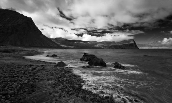 Svarthvít mynd af fjörunni í Hlöðuvík. Álfsfell til vinstri en Kjalárnúpur til hægri.